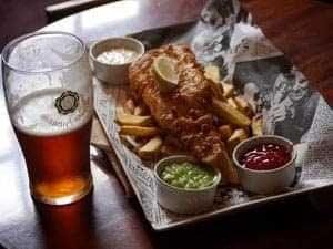 Pint of beer with fish and chips, and mushy peas