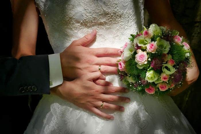 Image of Bride and Groom's hands on the bride's waist